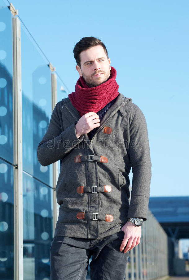 Casual young man walking outdoors in jacket and scarf stock photo
