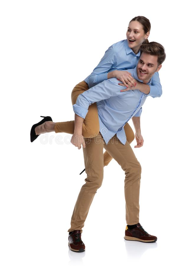 Young man carries woman on his back looking to side stock photo