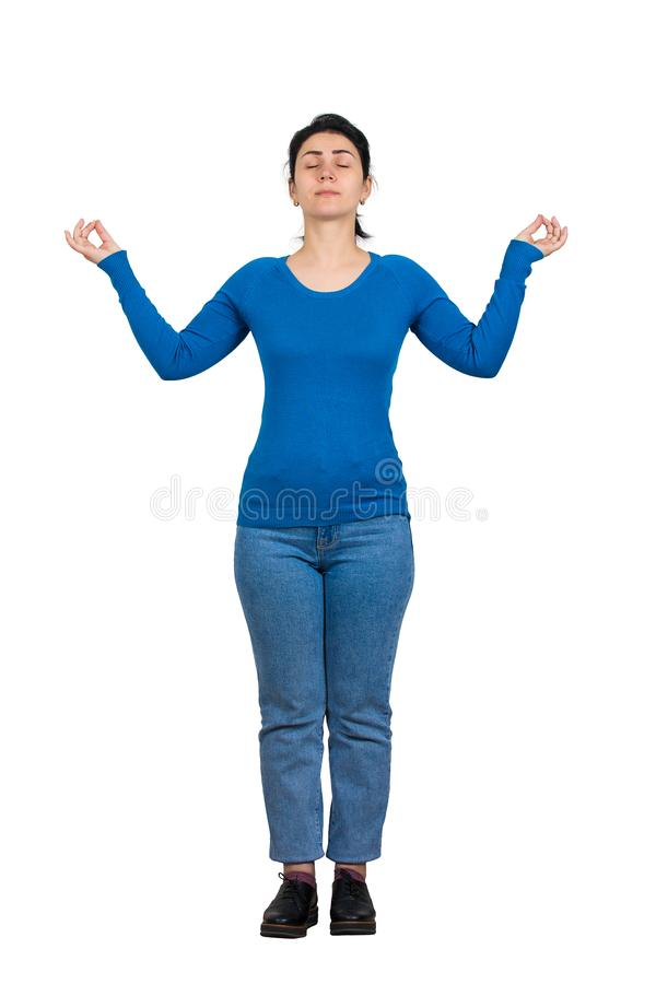 Casual young woman, eyes closed, raising hands showing zen gesture like practicing yoga. Relaxed girl meditate and calming down stock image