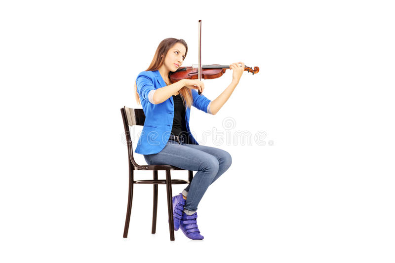 Casual young woman seated on a wooden chair playing the violin royalty free stock images