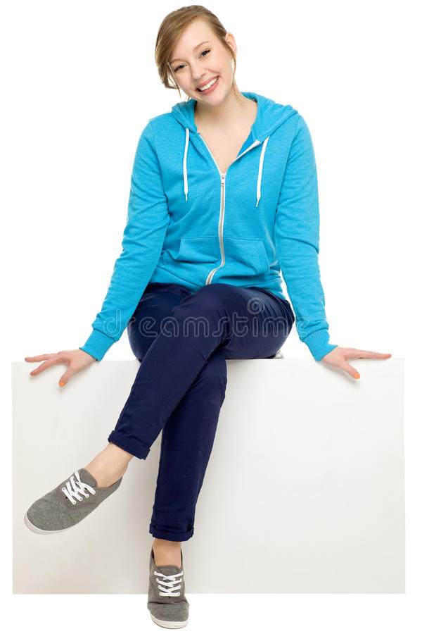 Casual young woman sitting on something stock photos