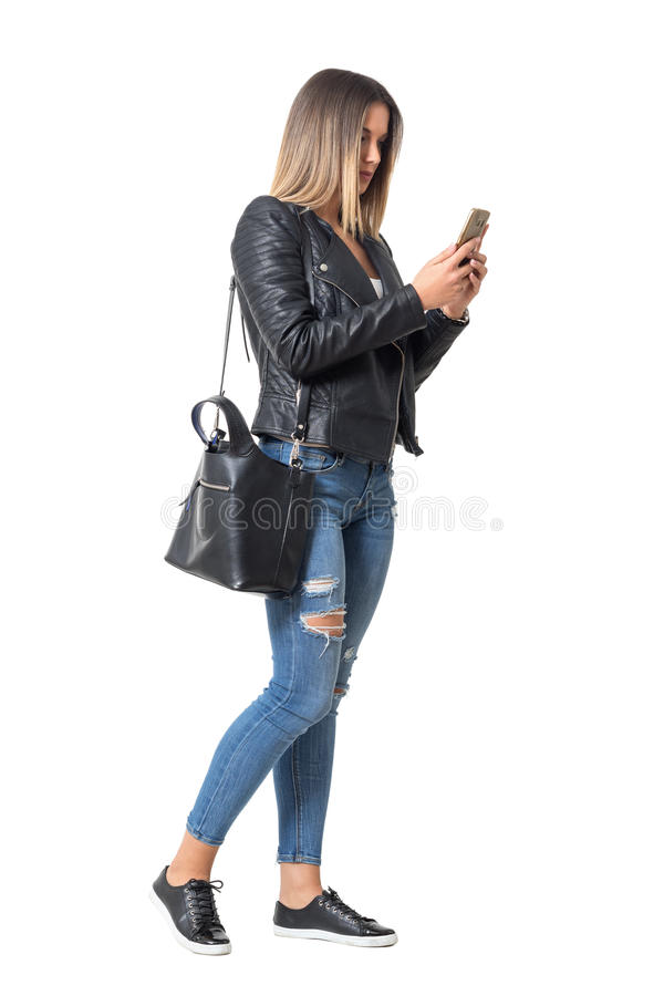 Casual young woman in street style clothing walking and typing on mobile phone. Full body length portrait isolated over white background royalty free stock photography