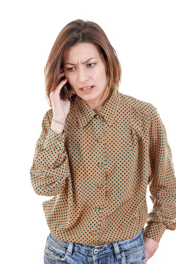 Casual young woman talking on the phone hearing bad news stock image