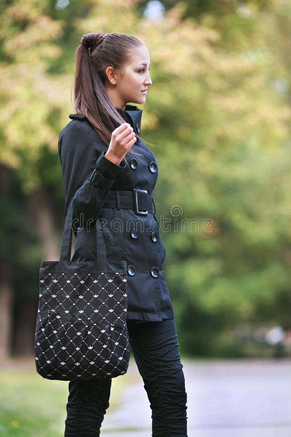 Casual young woman walking on the street royalty free stock photography