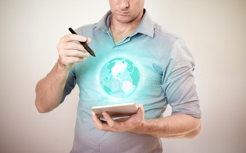 Casually dressed business man holding tablet with pen looking at projected virtual globe on plain background stock photography
