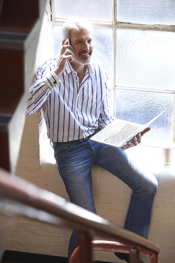Casually Dressed Businessman Working On Stairs In Office stock photography