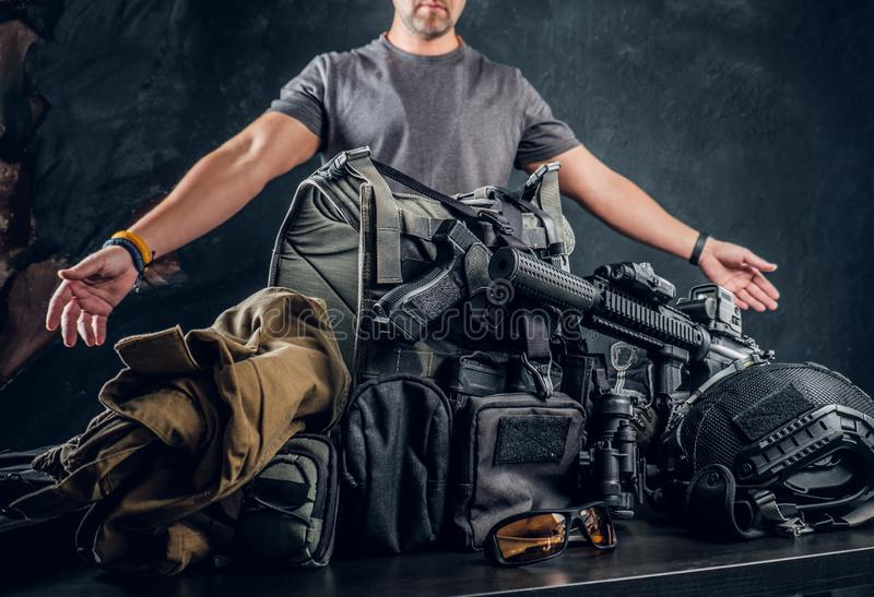 Casually dressed man showing his military uniform and equipment. Modern special forces equipment. Studio photo against a dark textured wall royalty free stock photography