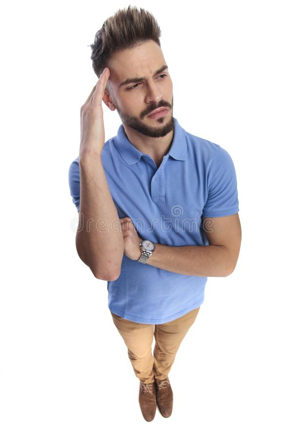 Casually dressed man wearing a light blue polo. Holding one hand around his forehead, while looking up and at a side stock photos
