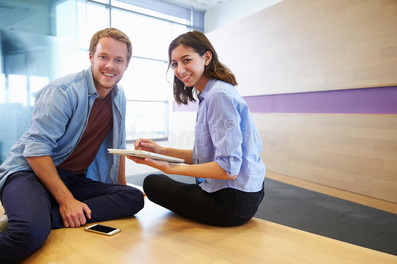 Casually dressed man and woman working together. Casually dressed men and women working together stock photos