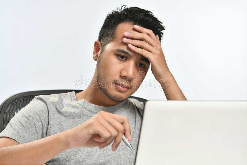 Startup business man holding his head looking stressed while working on a laptop stock photo