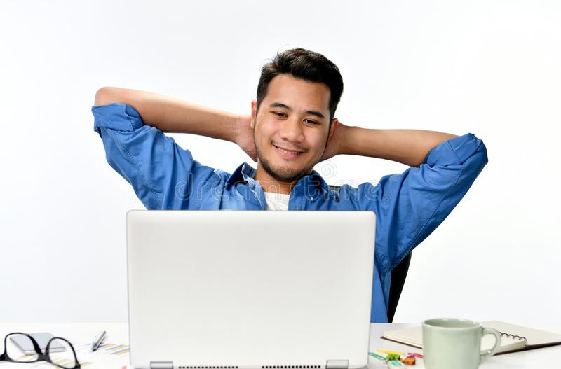 Startup business man sitting in relaxed posture after having work done easily. Casually-dressed startup business man sitting in relaxed posture after having work stock images
