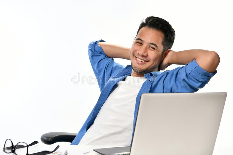 Startup business man sitting in relaxed posture after having work done easily. Casually-dressed startup business man sitting in relaxed posture after having work stock photography