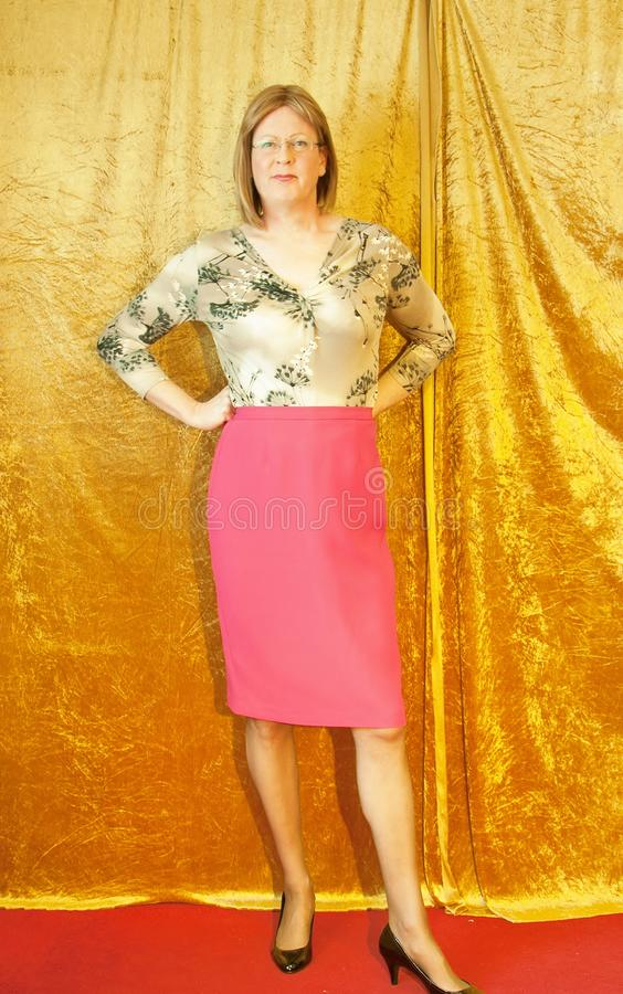 Smartly dressed Woman stood by curtain. A casually dressed Woman wearing a pattern blouse and a pink pencil skirt stood by a curtain royalty free stock photography