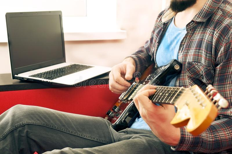 Casually dressed young man with guitar playing songs in the room at home. Online guitar lessons concept. Male guitarist practicing. Young man, hipster folk royalty free stock image