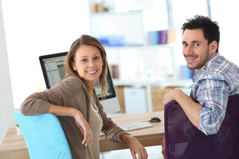 Casula smiling business people at office. Business people meeting in front of desktop stock photography
