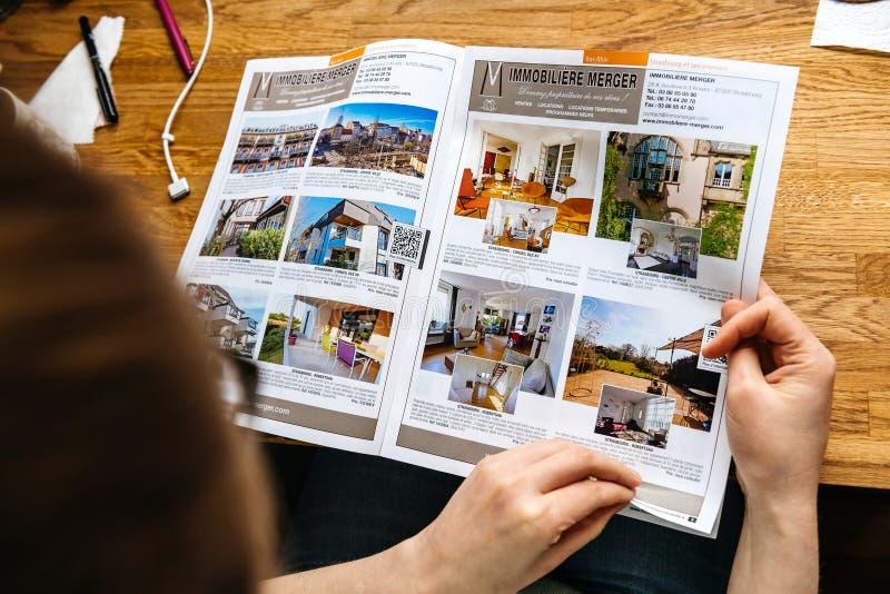 Catálogo de las propiedades inmobiliarias de las casas y de los apartamentos de la lectura del agente de la mujer imagen de archivo libre de regalías