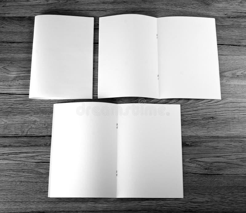Catálogo vazio, folheto, compartimentos, livro no fundo de madeira fotografia de stock