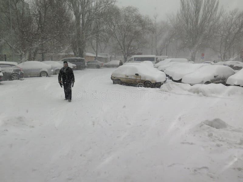 Catástrofes naturais nublado inverno, blizzard, estradas paralizadas nevadas fortes do carro da cidade, colapso Ciclone coberto d imagem de stock
