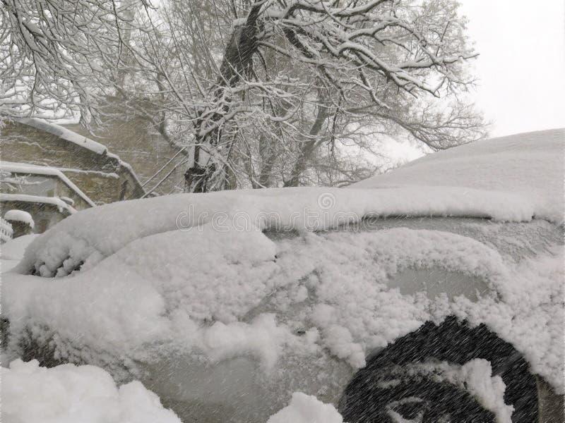 Catástrofes naturais nublado inverno, blizzard, estradas paralizadas nevadas fortes do carro da cidade, colapso Ciclone coberto d fotografia de stock royalty free