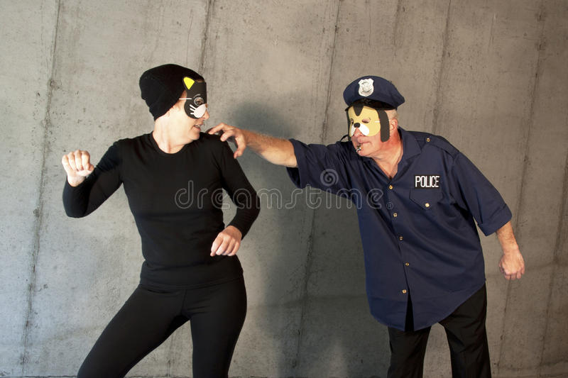 Cat Burglar Nabbed by Police Dog. Cat Thief being caught by a Dogged Law Officer royalty free stock image