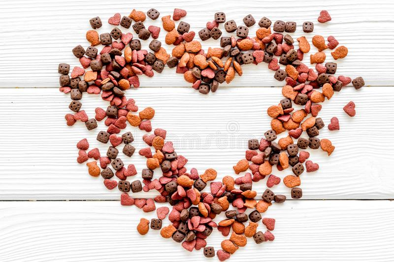 Cat dry food in heart shape on white wooden background top view royalty free stock images