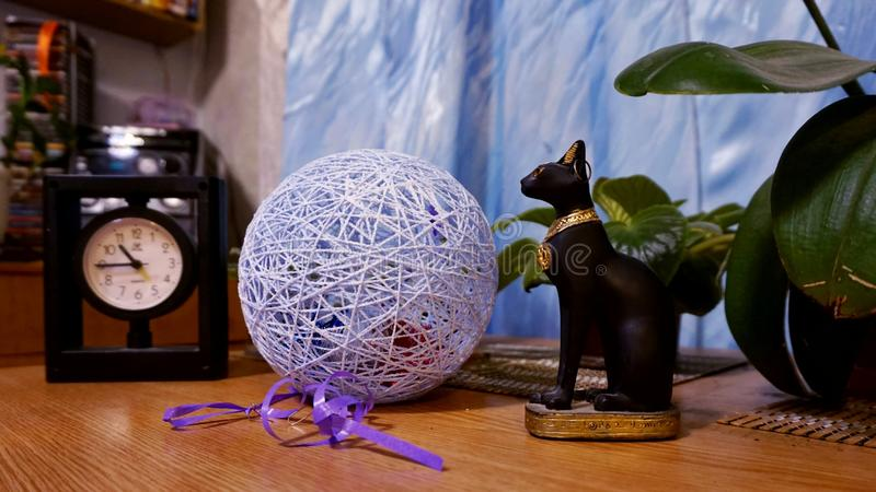 Cat figurine, thread ball and clock standing on the table in the house. Cat figurine, thread ball and clock standing on the table in the house royalty free stock image