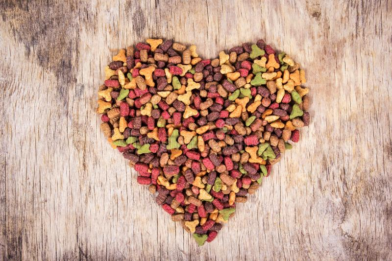 Cat food on wooden background. Cat food in the shape of heart. Top view stock photography