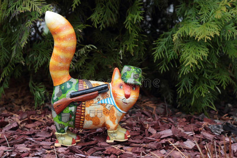 Cat hunter on a brown chipped. Cat the hunter with the gun on on brown chipped wood under a fir-tree. Plaster figure stock image