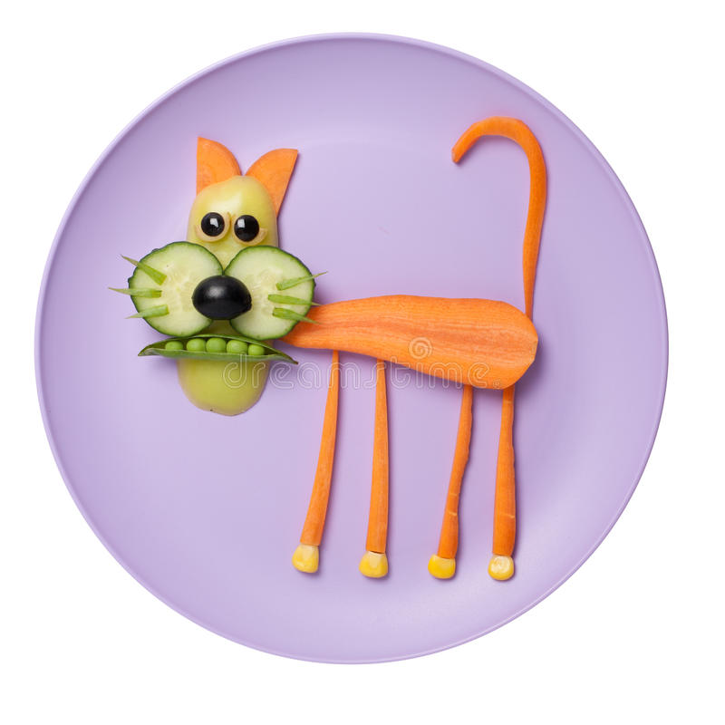Cat made of food on pink plate. Cat made of carrot, pepper, cucumber, corn, pea and olives. Shot with Canon 5D, ISO 100, on plate and white background royalty free stock photos