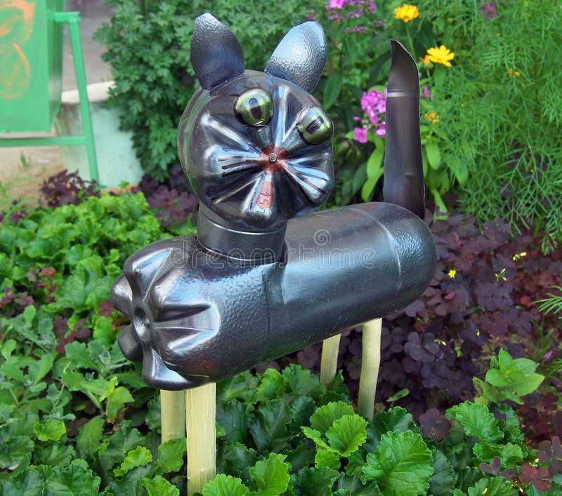 Cat made of used plastic bottles on a flower bed stock images