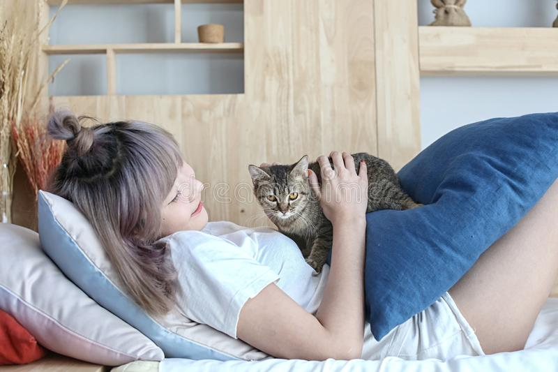 The cat on the purple pillow on body female. Young woman wearing warm T-shirt is resting with a cat on the arm at home. Girl stock image