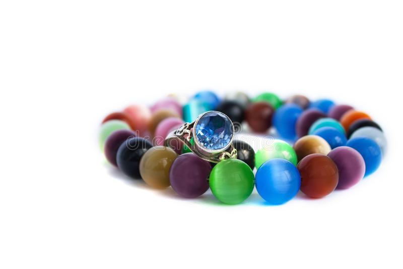 Cat`s eye quartz necklace and bracelet, selective focus on white background isolated. Colourful precious stones. Cat`s eye quartz necklace, bracelet and antique stock photos