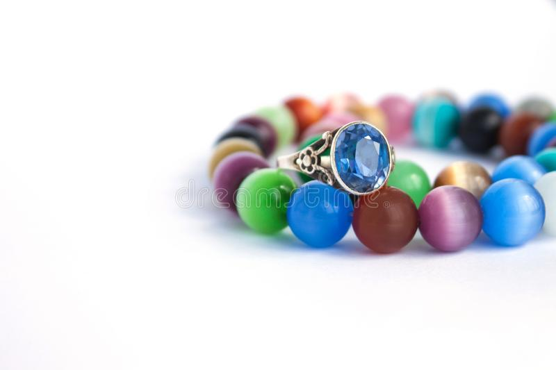 Cat`s eye quartz necklace and bracelet, selective focus on white background isolated. Colourful precious stones. royalty free stock photography
