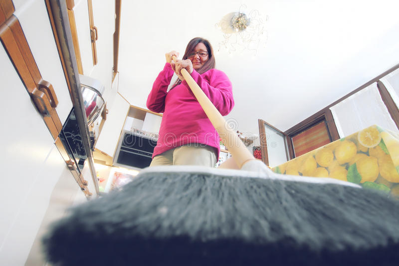 Cat's prospective. A woman drives away a cat from the kitchen. A woman drives away a cat with a broom from the kitchen stock photos