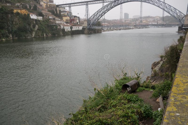 Cat shelters from rain in old metal barrel on banks of River Douro in Porto, Portugal with bridge in background. Cat shelters from rain in old metal barrel on stock images