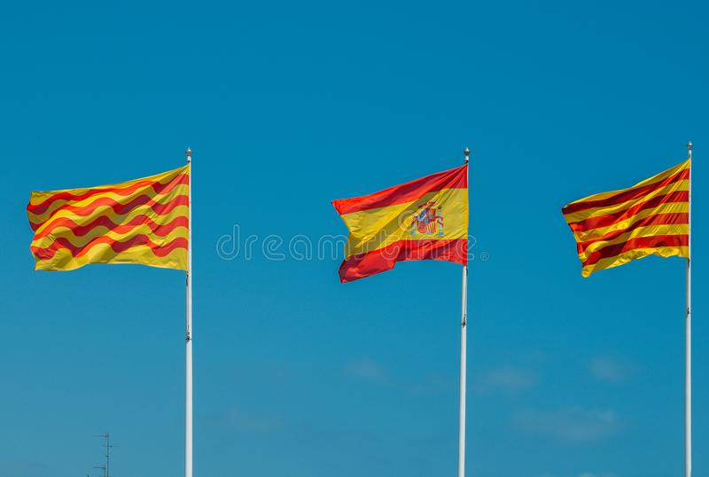 Catalaans, Spaans en Tarragonian markeert het vliegen op een mast tegen een blauwe hemel stock afbeelding