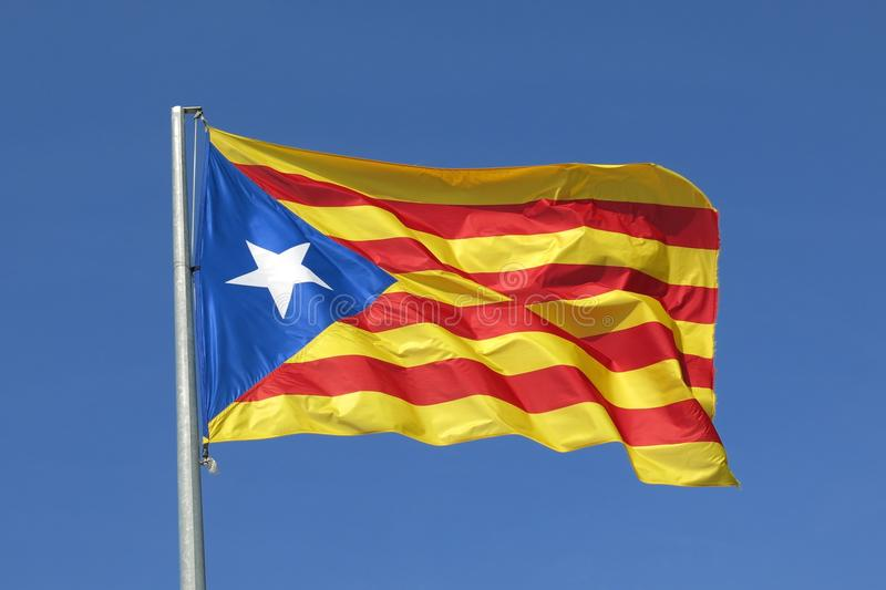 Catalan flag independence separatist flag waving in blue sky. The Catalan separatist independence flag waves proudly in a cloudless blue sky stock photo