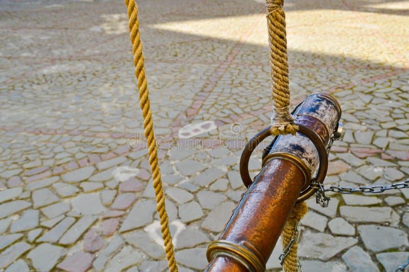 Catalejo antiguo marrón antiguo viejo del pirata atado con las cuerdas contra un fondo de las losas de piedra en el camino imagen de archivo