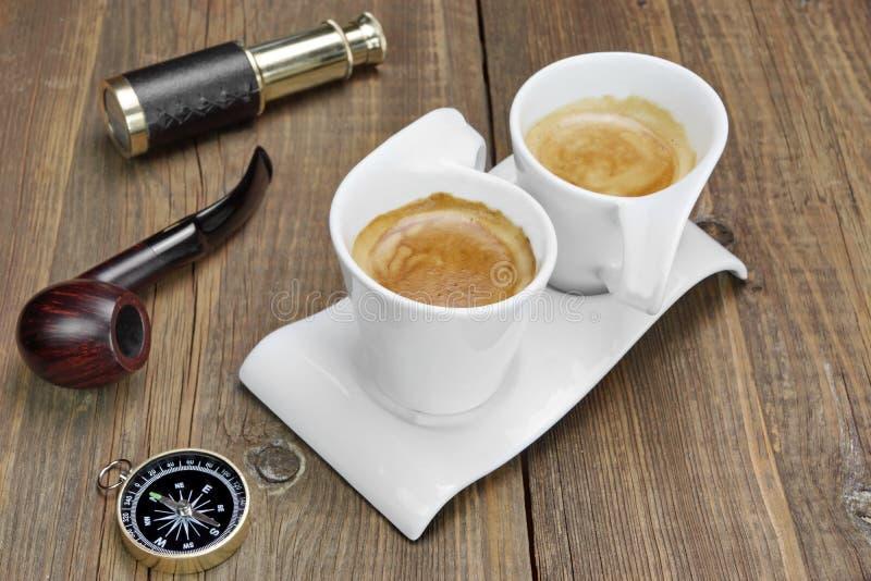 Catalejo, compás, tubo que fuma y café del café express de dos blancos foto de archivo libre de regalías
