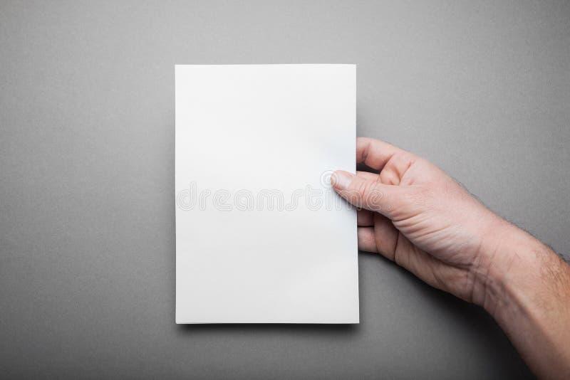 Catalogo vuoto dello spazio in bianco del modello, rivista, modello del libro in mano dell'uomo con le ombre molli su fondo grigi immagini stock