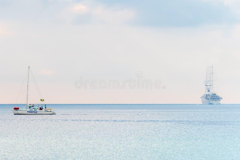 Catamar?n con la bandera jamaicana y un barco de cruceros en la navegaci?n del fondo de la costa de Montego Bay Jamaica imágenes de archivo libres de regalías