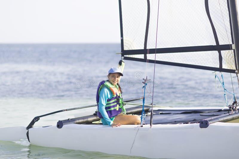 Catamarán hermoso de la navegación del adolescente en puesta del sol hermosa imagenes de archivo