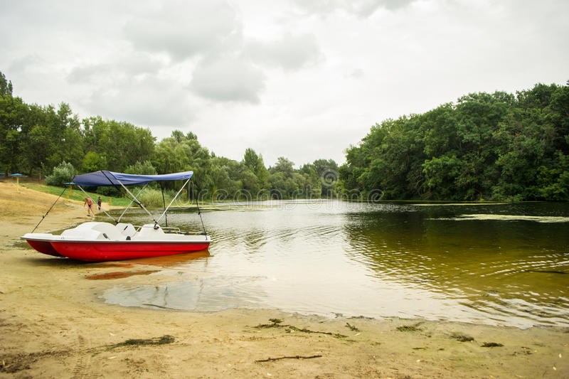 Catamaran on the bank of the lake. Beautiful landscape of the lake with red-yellow catamaran in the foreground stock photography
