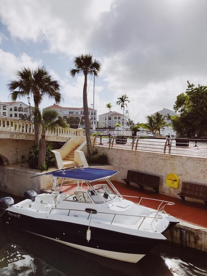 Catamaran with blue roof moored in cap Cana marina. In Atlantic Ocean against luxury residence with palms under the cloudy sky stock image