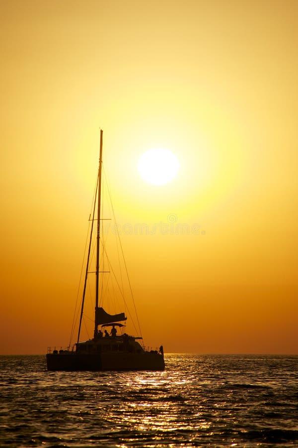Catamaran die bij zonsondergang vaart stock afbeeldingen