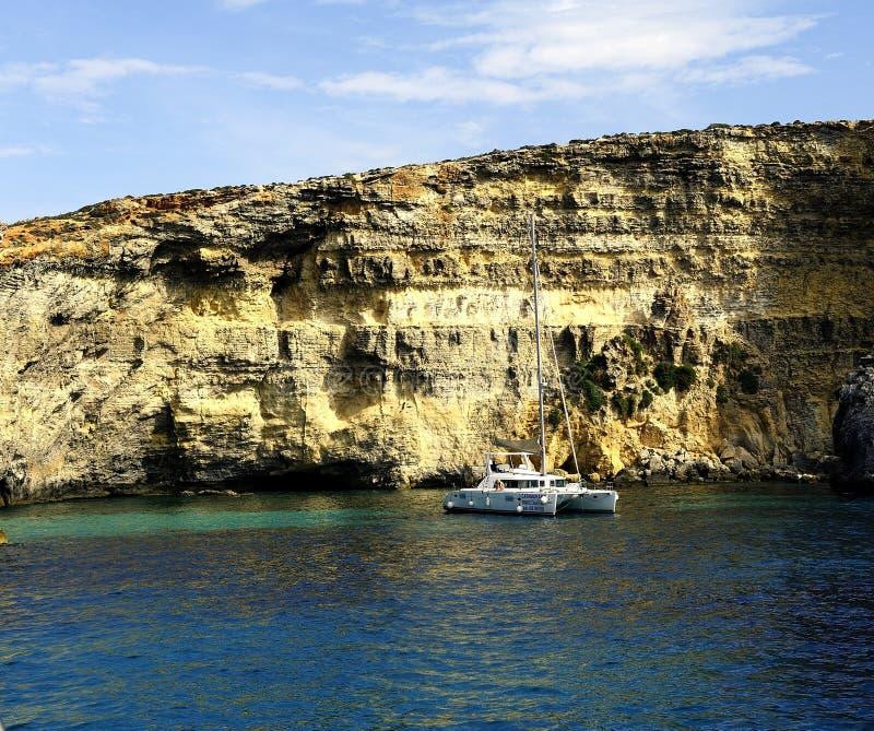 Catamaran przy kotwicą pod falezami Comino obraz royalty free