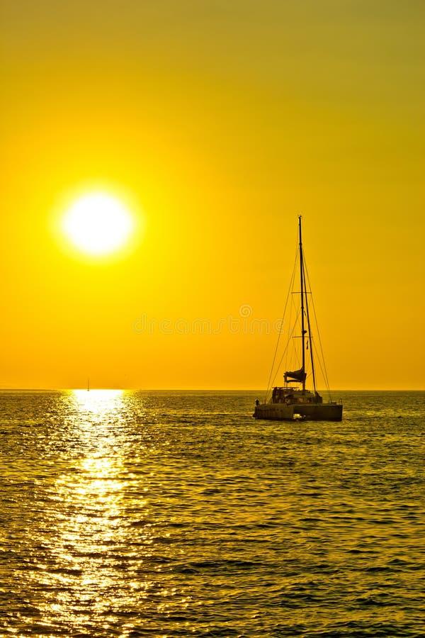 Catamaran sailboat at golden sunset stock photo