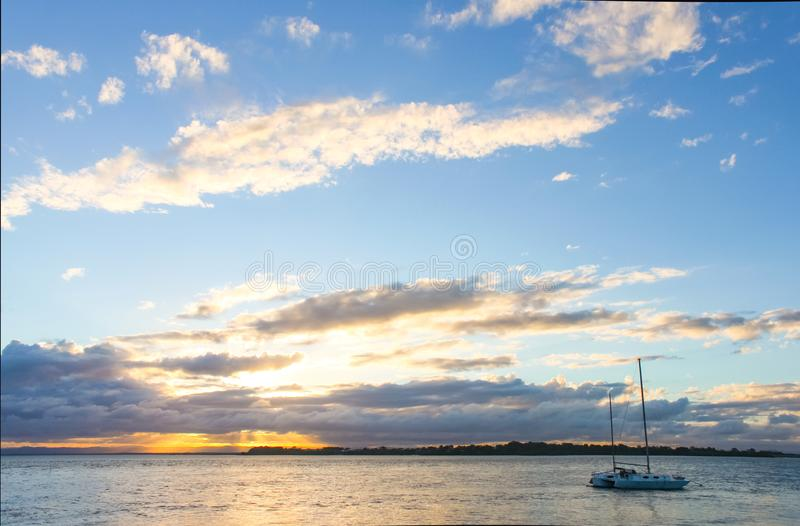Catamaran sailboat in water at sunset with sun breaking though clouds on horizon royalty free stock images