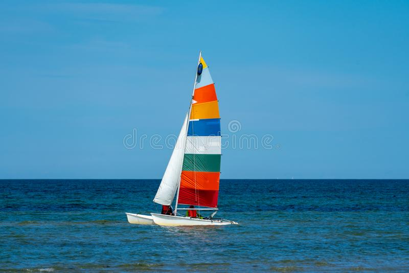 Catamaran sailing boat with a very colourful sail stock photo