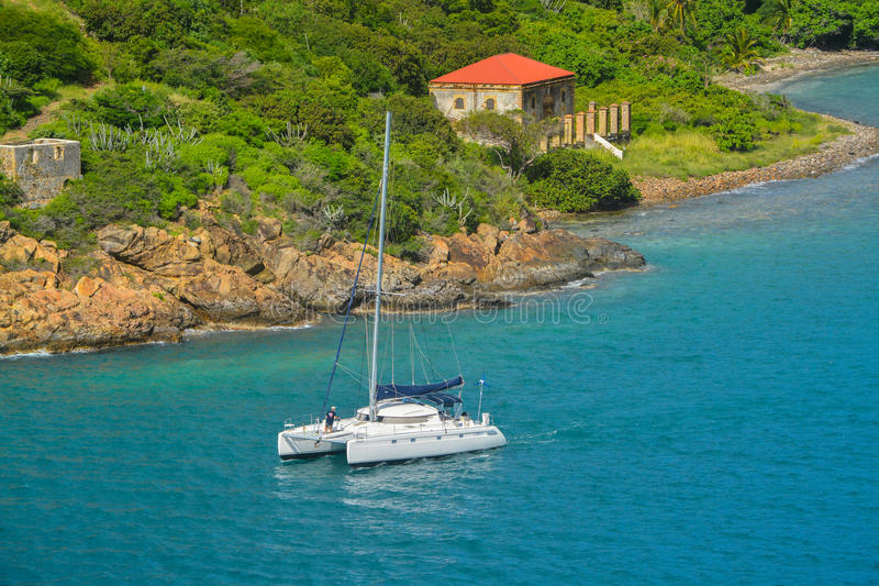 Catamaran sailing by Garrison House at Fort Willoughby on Hassel Island, St Thomas U.S. Virgin Islands. A catamaran sailing by Garrison House at Fort Willoughby royalty free stock photography